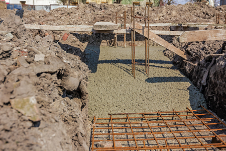 concreting: Concrete is flowing over reinforcement at the base of new building.