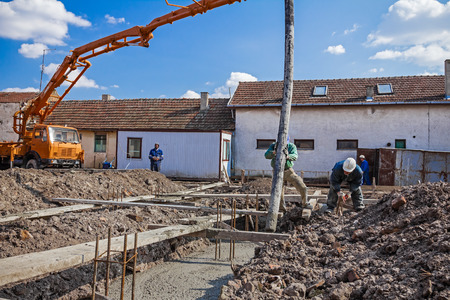 concreting: Construction workers are pulling large hose for concreting of steel reinforced concrete on construction site. Stock Photo