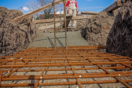 trenching: Concrete is flowing over reinforcement at the base of new building.
