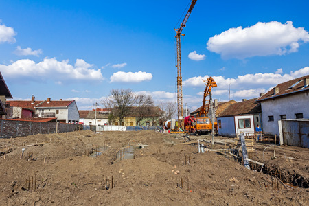 erector: Landscape of construction site, workers are preparing for casting base of residential building. Stock Photo