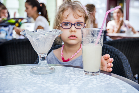 blithe: Little cute girl with glasses is drinking lemonade at pastry shop in summertime.