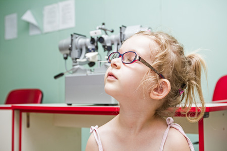 nearsighted: Little girl is at the eye examination showing directions of signs on board. Stock Photo
