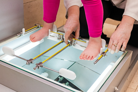 foot doctor: Doctor orthopedist is measuring childs foot with adjustable metal rulers.