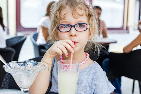 pastry shop: Little cute girl with glasses is drinking lemonade at pastry shop in summertime.