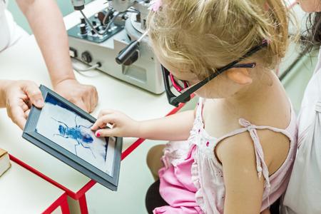 oculista: Opticos en su consulta está dando prueba de niña de los ojos, el tratamiento de la vista por el oculista.