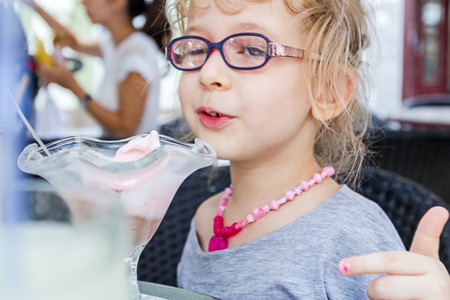 blithe: Little cute girl with glasses is eating ice cream at pastry shop in summertime. Stock Photo