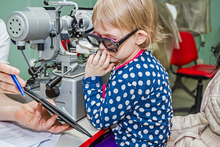oculist: Opticos en su consulta está dando prueba de niña de los ojos, el tratamiento de la vista por el oculista.