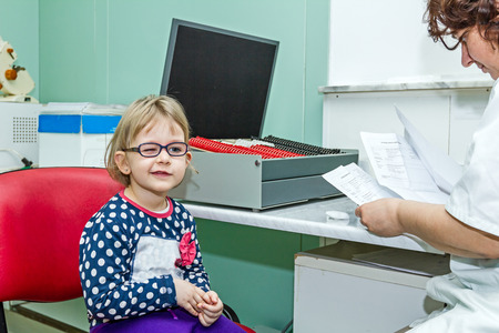 Little girl is at the eye examination showing directions of signs on board. Stock Photo
