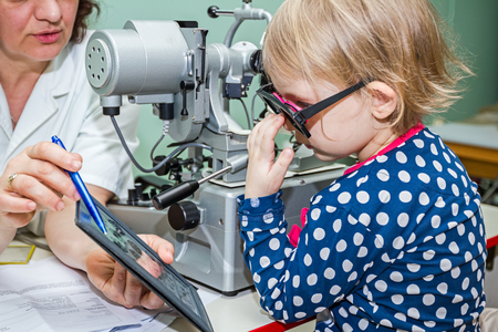 Optician in his surgery is giving girl eye test, treatment of eyesight by the oculist.