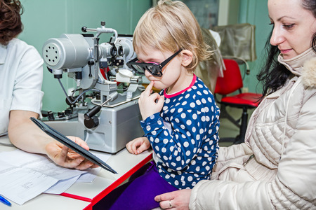 oculist: Optician in his surgery is giving girl eye test, treatment of eyesight by the oculist.