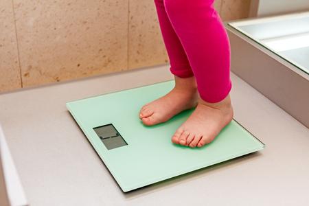 Il bambino è con i suoi piedi nudi in piedi su una scala bagno sottile di vetro.