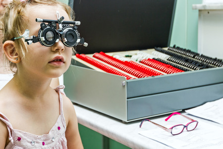 Young girl stand still while undergoing eye test with phoropter.