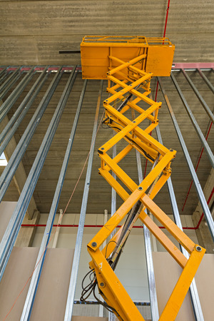 bulkhead: Workers are high up in cherry picker on building site. Stock Photo