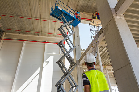 Boss control workers in scissor lift platform on a construction site. Standard-Bild