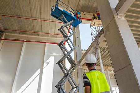 Boss control workers in scissor lift platform on a construction site. Standard-Bild