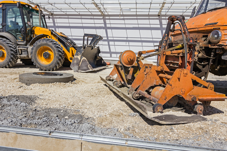 compacting: Plate compactor is mounted to the truck, compacting sand at road construction site. Stock Photo