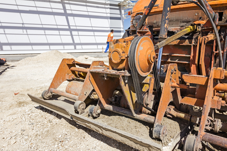 vibrating: Plate compactor is mounted to the truck, compacting sand at road construction site. Stock Photo