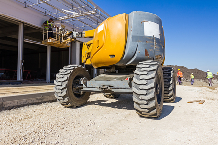 erector: Cherry picker is moving over sandy ground at construction site. Stock Photo