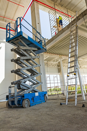 Workers are high up in cherry picker on building site. Stock Photo - 55391573