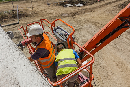 High elevated cherry picker with team of workers on construction site. Standard-Bild