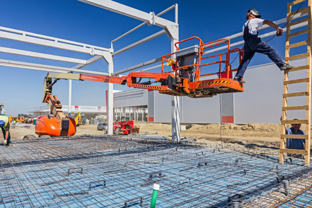 Construction worker is welding metal frame without proper safety equipment on wooden leaders.