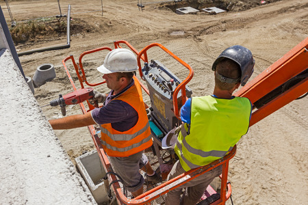 High elevated cherry picker with team of workers on construction site. Stock Photo