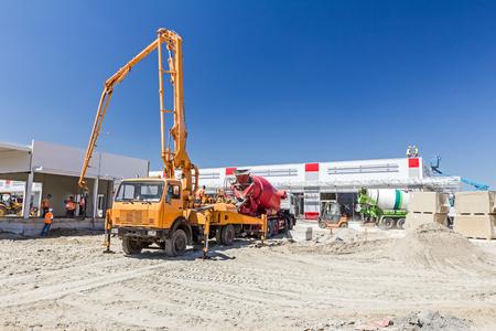 concrete pump: Truck mixer is pouring concrete into concrete pump for casting.