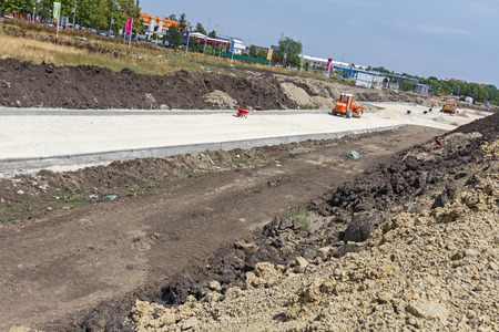 leveler: Grader is working on gravel leveling for the new road on construction site. Stock Photo