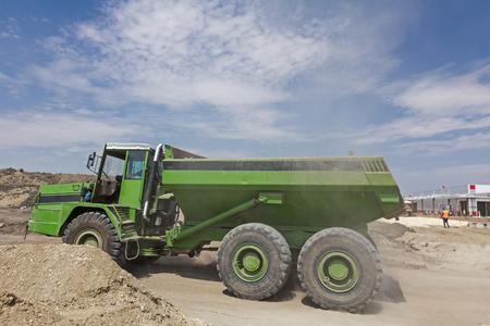 dumper truck: Dumper truck is going to unload soil or sand at construction site.
