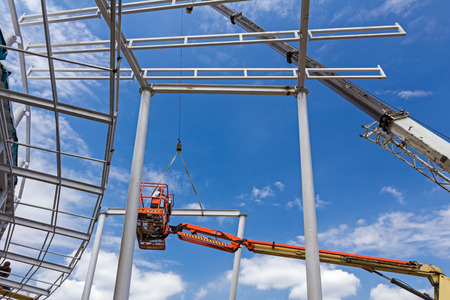 Height worker is helping to the mobile crane to place part on building skeleton. Standard-Bild