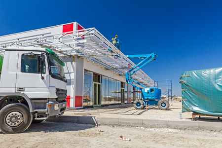 picker: High elevated cherry picker with team of workers on construction site. Stock Photo