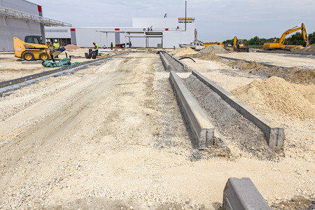 kerb: Kerb stones are lined on gravel ground for placing parking area edge at construction site.