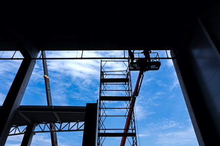 picker: Workers are high up in cherry picker on building site. Stock Photo