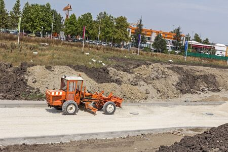 Grader is working on gravel leveling for the new road on construction site. Stock Photo