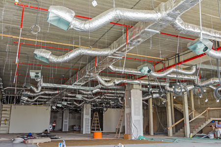 Ventilation pipes in silver insulation material hanging from the ceiling inside new building. Stockfoto