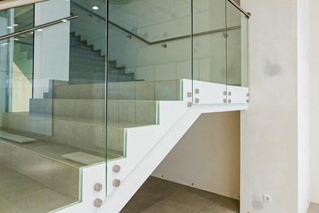 Detail on stairway with glass railing in a new modern building.
