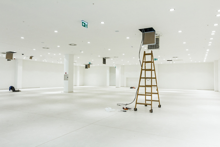 air duct: Workers are used wooden ladder to complete conditioning system ventilation at modern office ceiling with air duct and lamps. Stock Photo