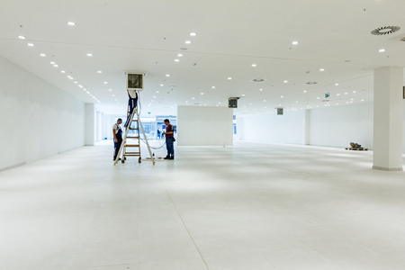 Workers are used wooden ladder to complete conditioning system ventilation at modern office ceiling with air duct and lamps. 스톡 콘텐츠