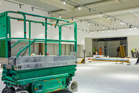 Scissor lift platform is inside of new big hall in building process. Stock Photo
