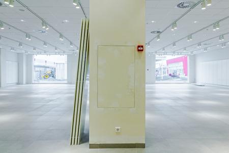 undone: Big yellow pillar in empty unfinished modern mega market. Architecture concept.