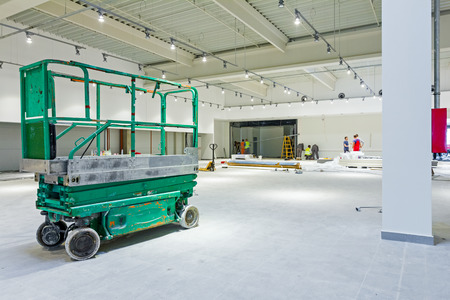 rigger: Scissor lift platform is inside of new big hall in building process. Stock Photo