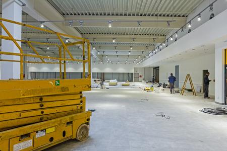 Scissor lift platform is inside of new big hall in building process. 스톡 콘텐츠