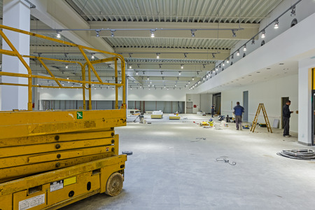 Scissor lift platform is inside of new big hall in building process. Stok Fotoğraf