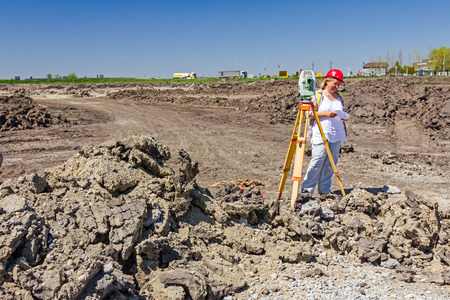 surveying: Woman surveying is measuring level on construction site. Surveyors ensure precise measurements before undertaking large construction projects.