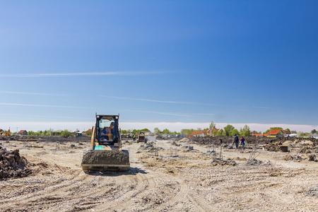 mini loader: Small excavator bobcat is transport gravel in his bucket over building site.