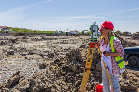 geodesist: Woman surveying is measuring level on construction site. Surveyors ensure precise measurements before undertaking large construction projects.