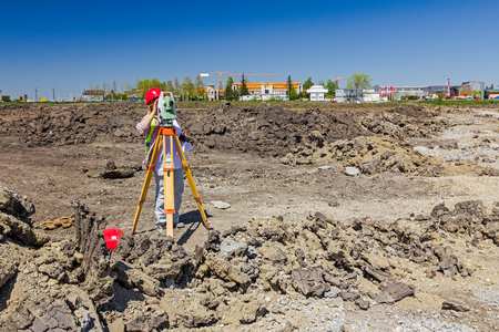 undertaking: Woman surveying is measuring level on construction site. Surveyors ensure precise measurements before undertaking large construction projects.