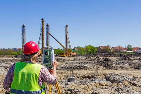 ensure: Woman surveying is measuring level on construction site. Surveyors ensure precise measurements before undertaking large construction projects.