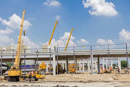 rock wool: Mobile crane is loading cargo. View on construction site with machinery, people at work.