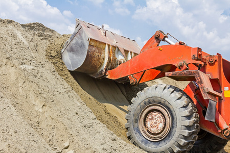 front end loader: Red loader with wheels at earthmoving works. Bulldozer is pushing sand on huge pile.